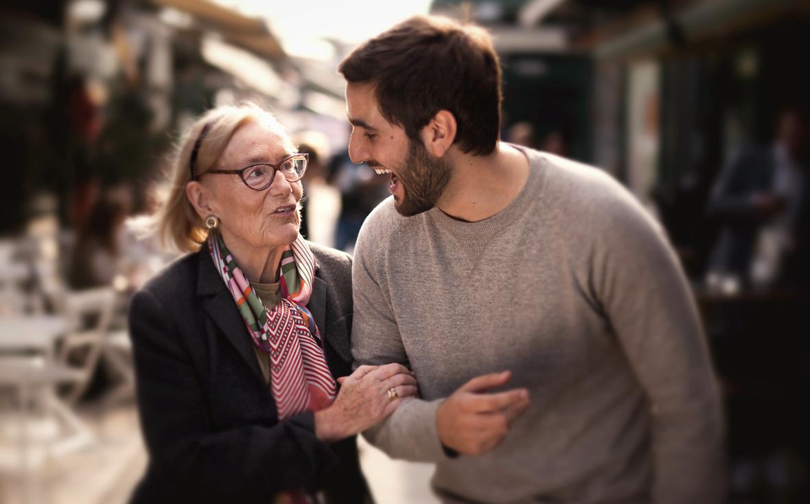 Eine ältere Dame geht Arm in Arm mit einem jungen Mann spazieren