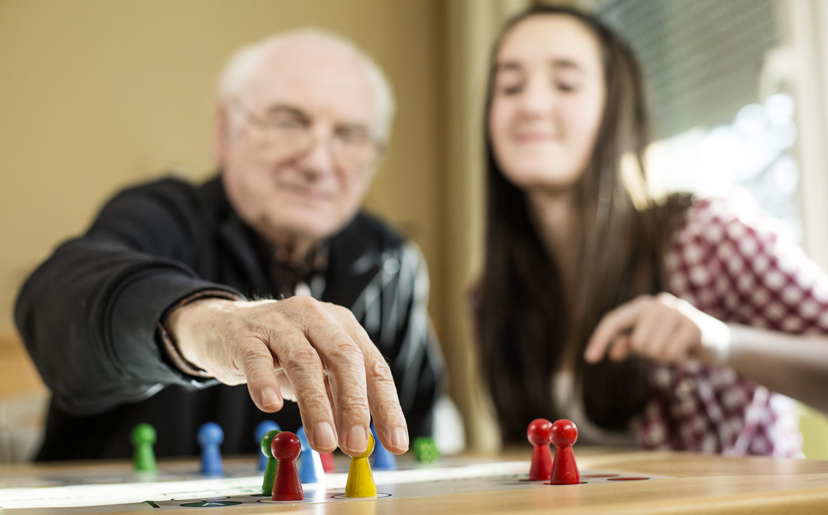 Ein älterer Mann spielt mit einer jungen Frau Mensch ärgere dich nicht.