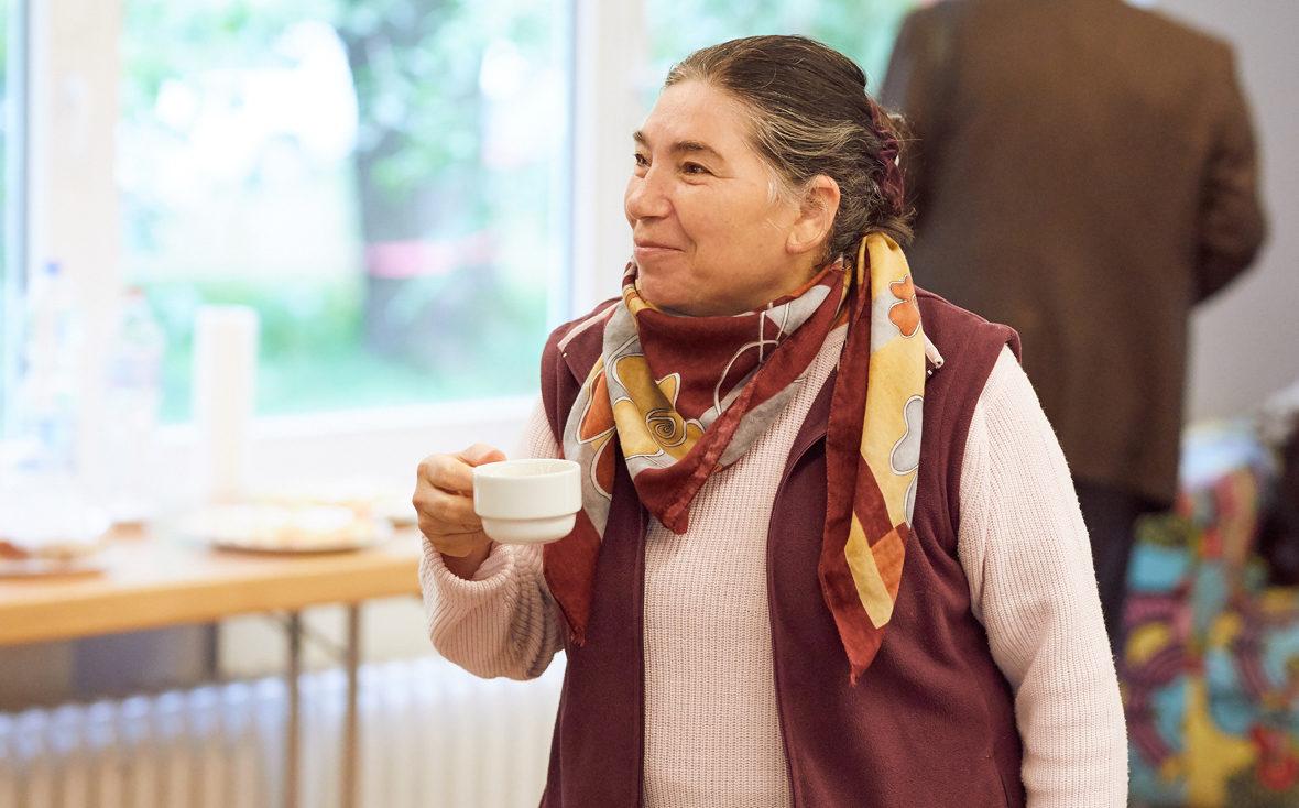 """Eine Teilnehmerin des Demenz-Theaters """"Vergissmeinnicht"""" trinkt eine Tasse Kaffee."""