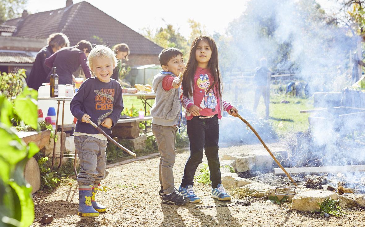 Kinder stehen am Lagerfeuer.