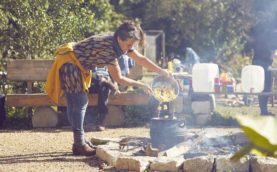 Frau kippt Kartoffeln in einen Topf auf dem Lagerfeuer.