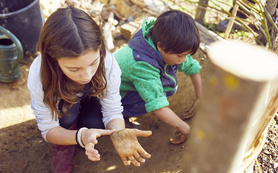 Kinder sitzen im Lehm und haben dreckige Hände.