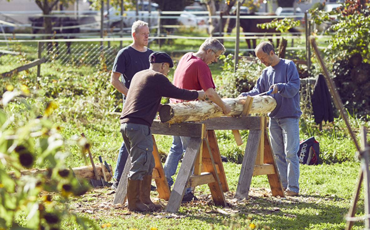 Vier Männer entrinden einen Baumstamm.