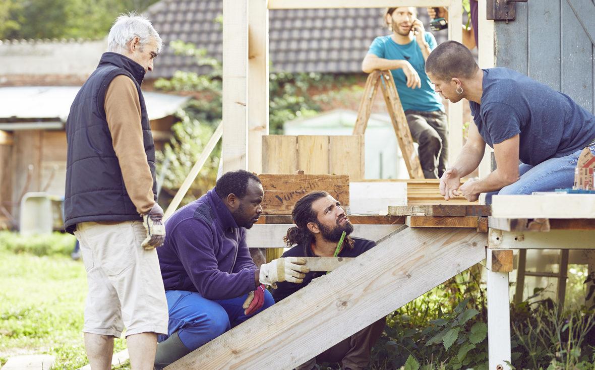 Vier Männer arbeiten an der Treppe zur Komposttoilette.