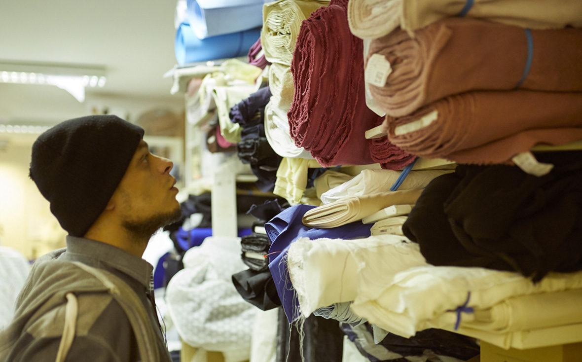 Habib schaut sich im Mode-Atelier die Stoffe an.