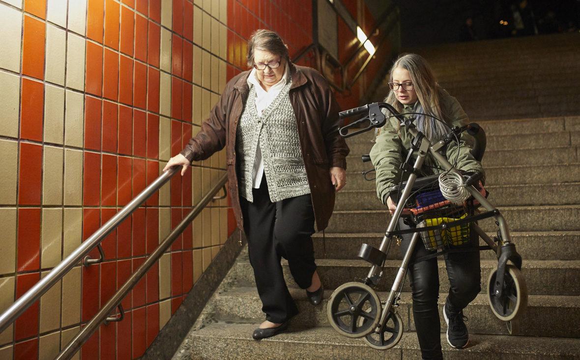 Kulturisten Hoch2: Julia trägt Frau Rieper den Rollator die Treppe runter.