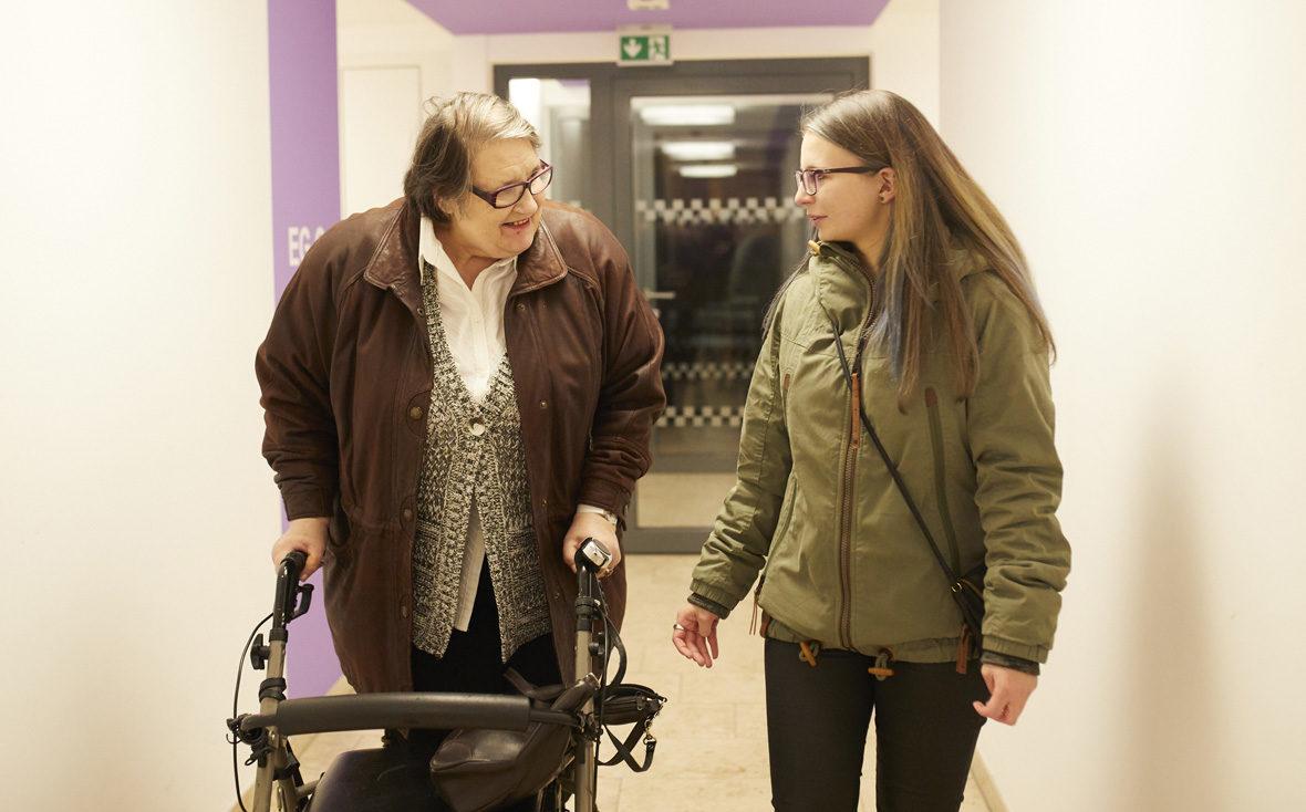 Eine Seniorin am Rollator geht mit einer Schülerin durch einen HAusflur.