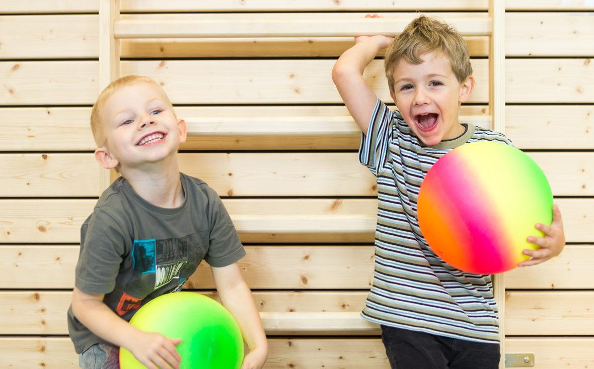 Zwei Jungen spielen in der Turnhalle mit bunten Bällen.