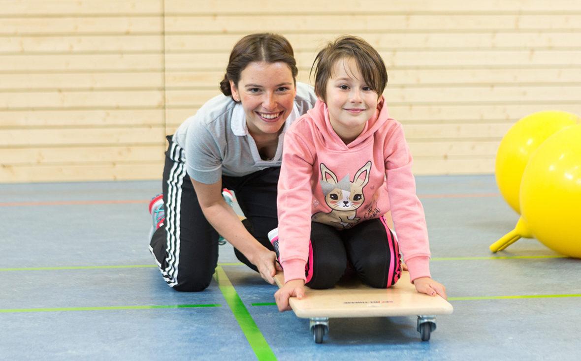 Physiotherapeutin Marleen Reuter mit einem Kind auf einem Rollbrett.