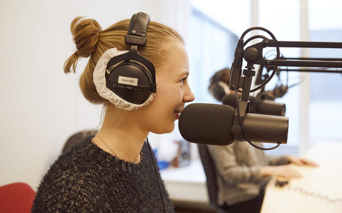 """Klinikradio Rio: Eine Patientin am Mikrofon, auf den Kopfhörern steht """"Radio Rio""""."""