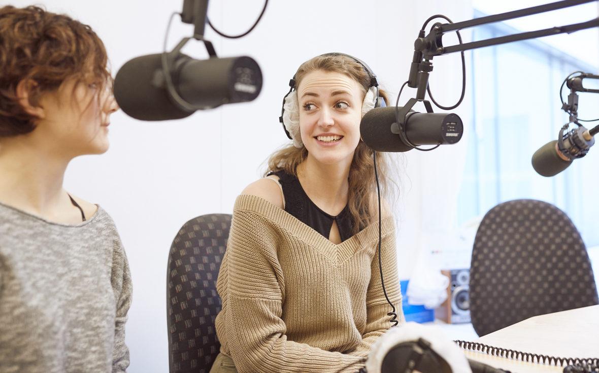 Klinikradio Rio: Zwei Patientinnen sitzen vor den Mikrofonen und schauen sich an.