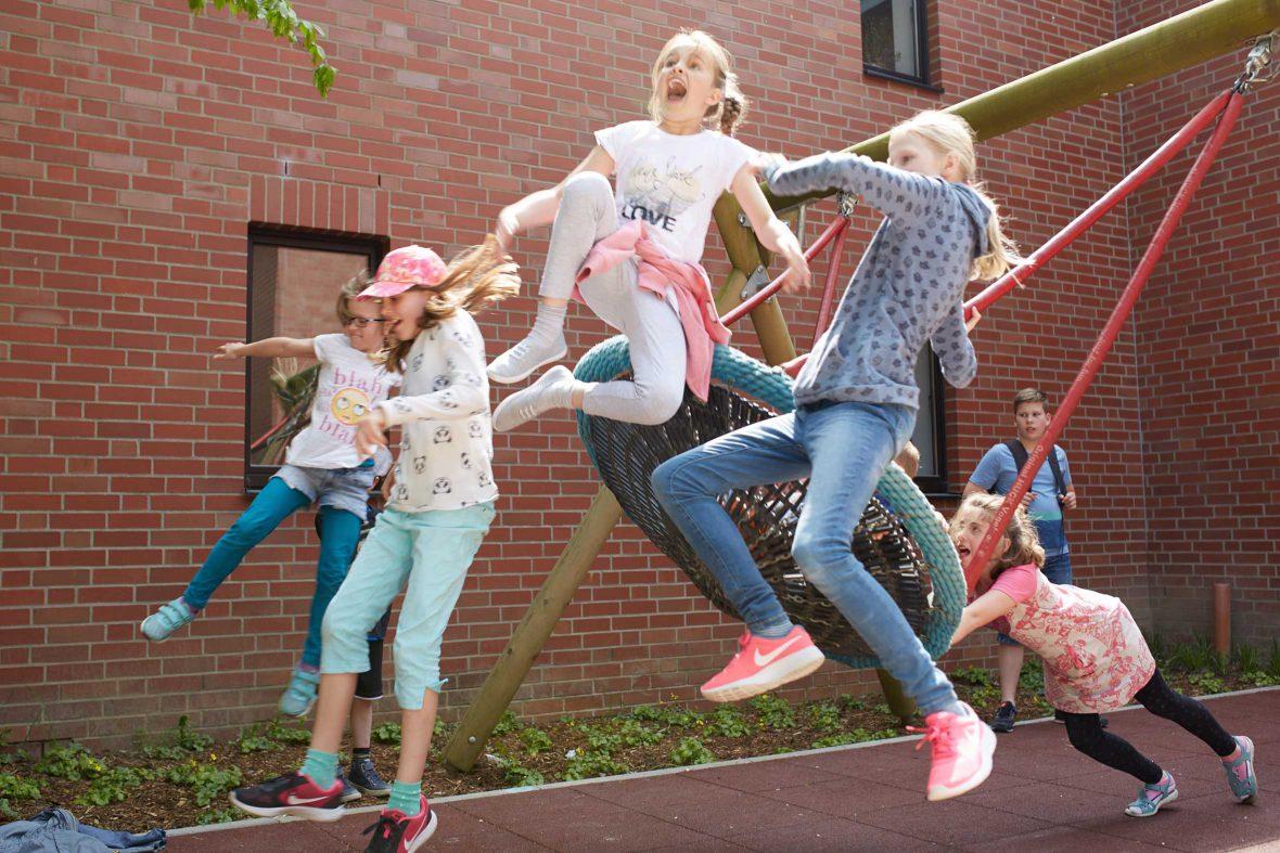 Kinder springen von der schwingenden Schaukel.