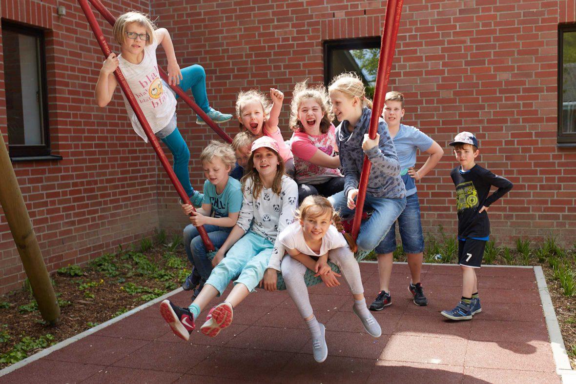 Kinder sitzen in einer großen Schaukel und holen Schwung.