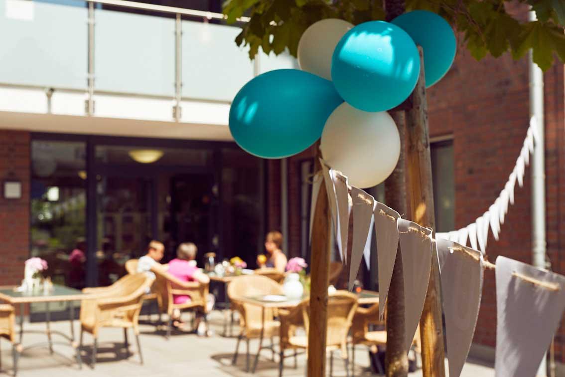 Im Garten-Café im Mehrgenerationenhaus Mathildenstift hängen Luftballons und Girlanden.