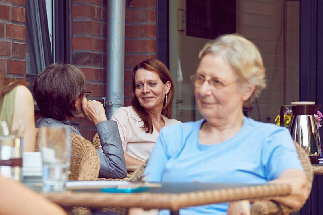 Im Hintergrund von Marianne Paschen sitzen zwei Frauen, die sich unterhalten.