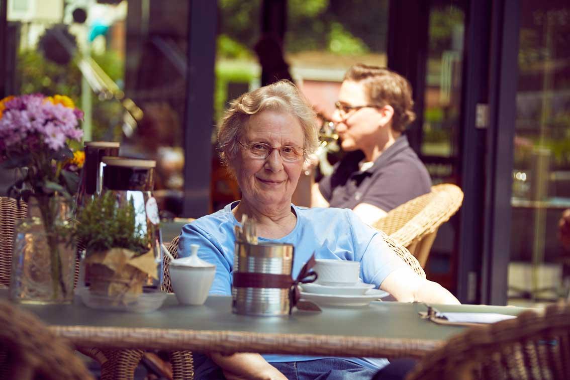 Marianne Paschen sitzt am Tisch im Garten des Garten-Cafés im Mehrgenerationenhaus Mathildenstift Münster