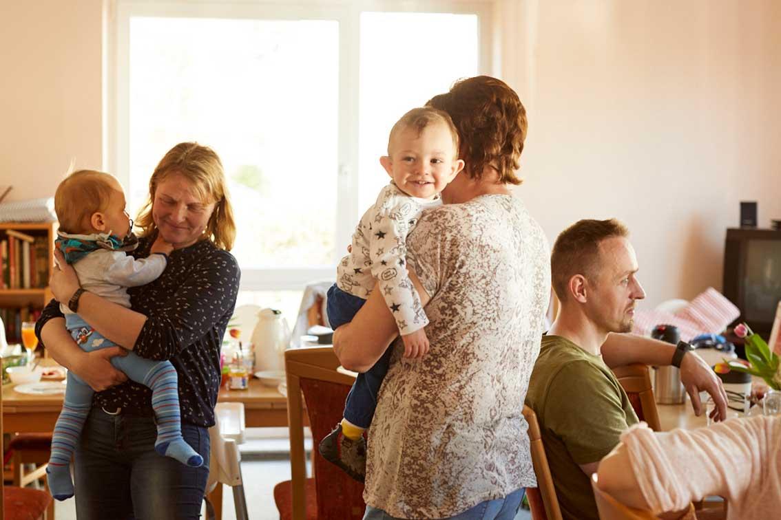 Zwei Kinder auf dem Arm zweier Frauen, eines schaut in die Kamera und lacht.