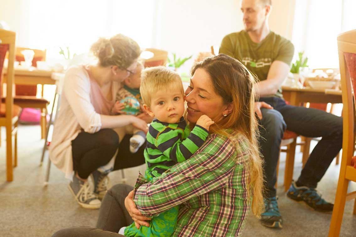 Eine Mutter hält ihr Kleinkind auf dem Arm und sieht es liebevoll an, das Kind schaut in die Kamera.