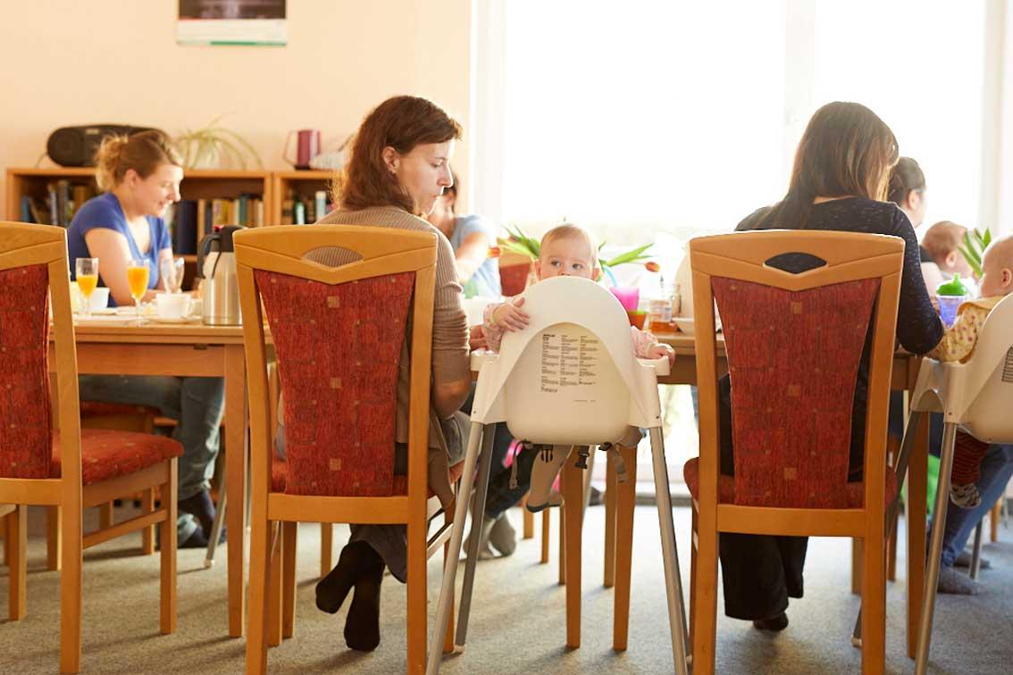Ein Kleinkind schaut über den Rand seines Stuhls beim Kreativfrühstück in Schwarzenberg.