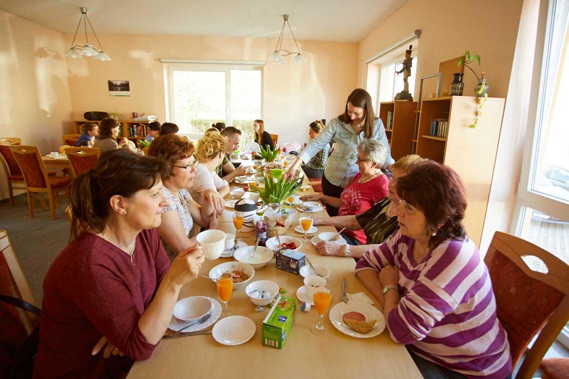 An einer langen Tafel sitzen die Nachbarn in Schwarzenberg zusammen, Quartiersmanagerin Sarah Meyer gießt Kaffee ein.