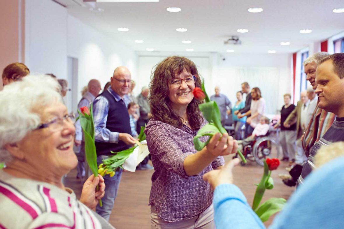 Tanzlehrerin Annelie überreicht jedem Teilnehmer eine Tulpe am Ende des Tanztees.