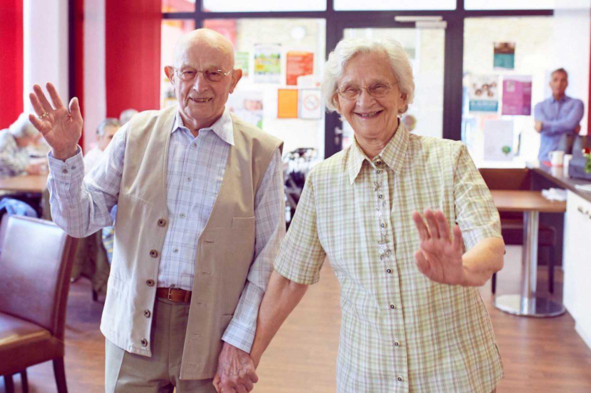 Zwei Besucher des Tanztees winken lachend und halten sich an der Hand.