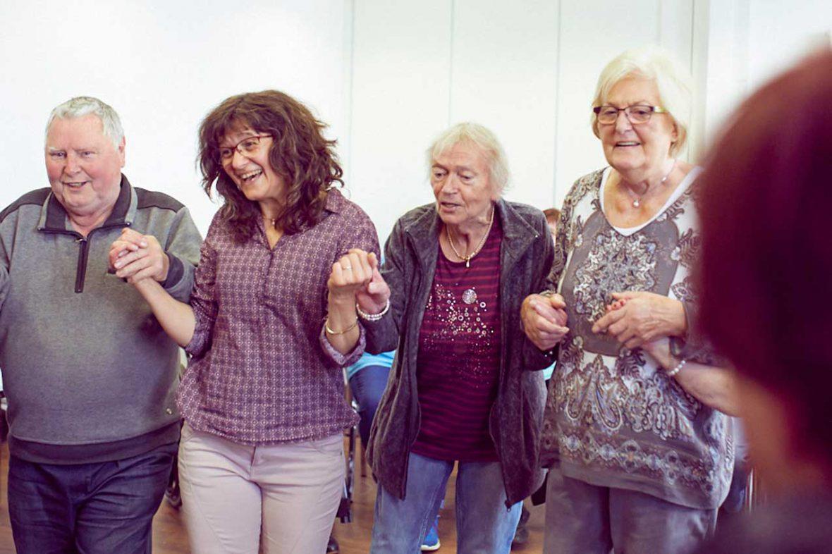 Tanztherapeutin Annelie hält zwei ältere Menschen an den Händen und tanzt mit ihnen.