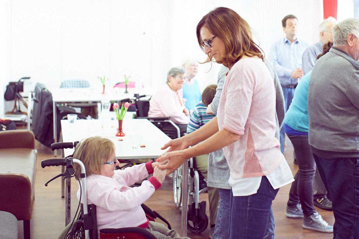Auch im Rollstuhl tanzen ist kein Problem: Eine Frau hält eine andere, die im Rollstuhl sitzt, an den Händen.
