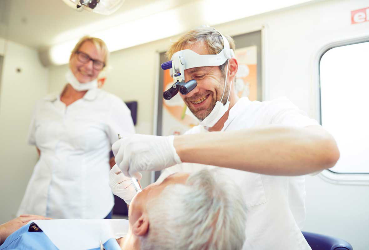 Dr. Uphoff trägt im Caritas Zahnmobil Hamburg einem Patienten eine Salbe auf das Zahnfleisch auf