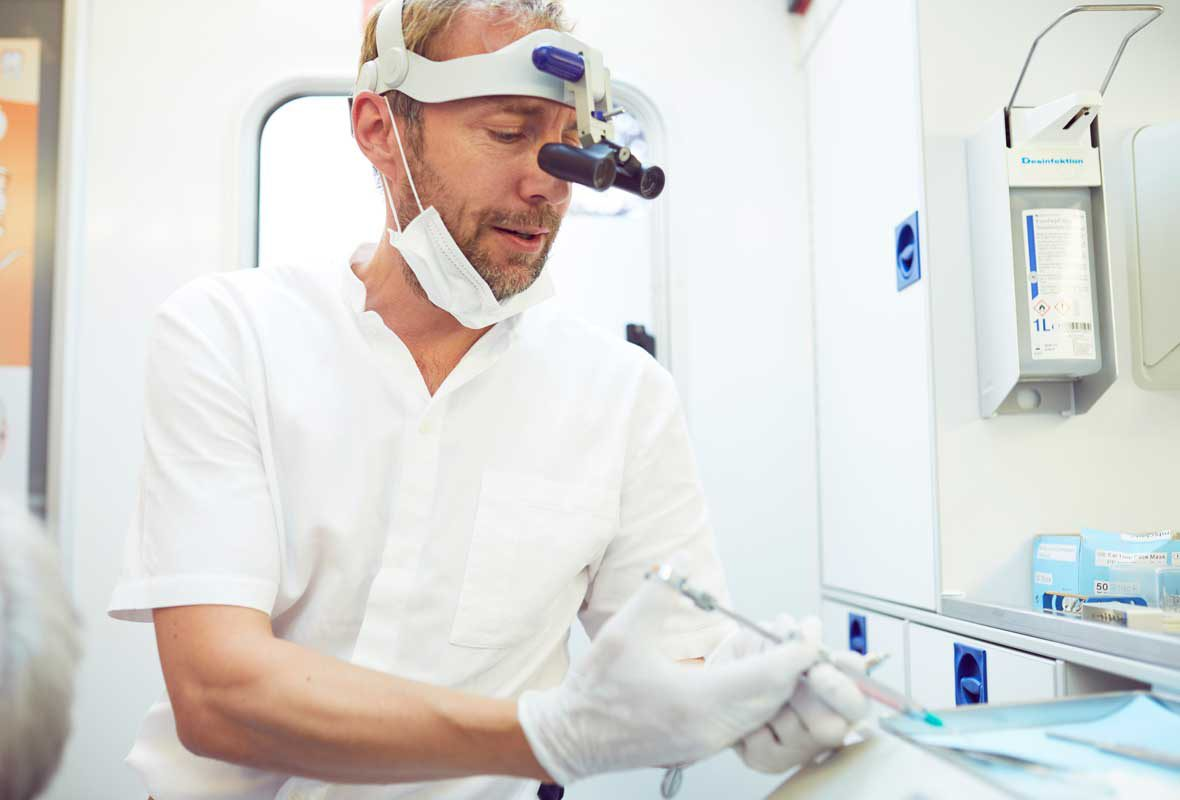 Dr. Uphoff bereitet im Zahnmobil Hamburg eine Salbe vor, die er seinem Patienten auf das Zahnfleisch aufrägt.