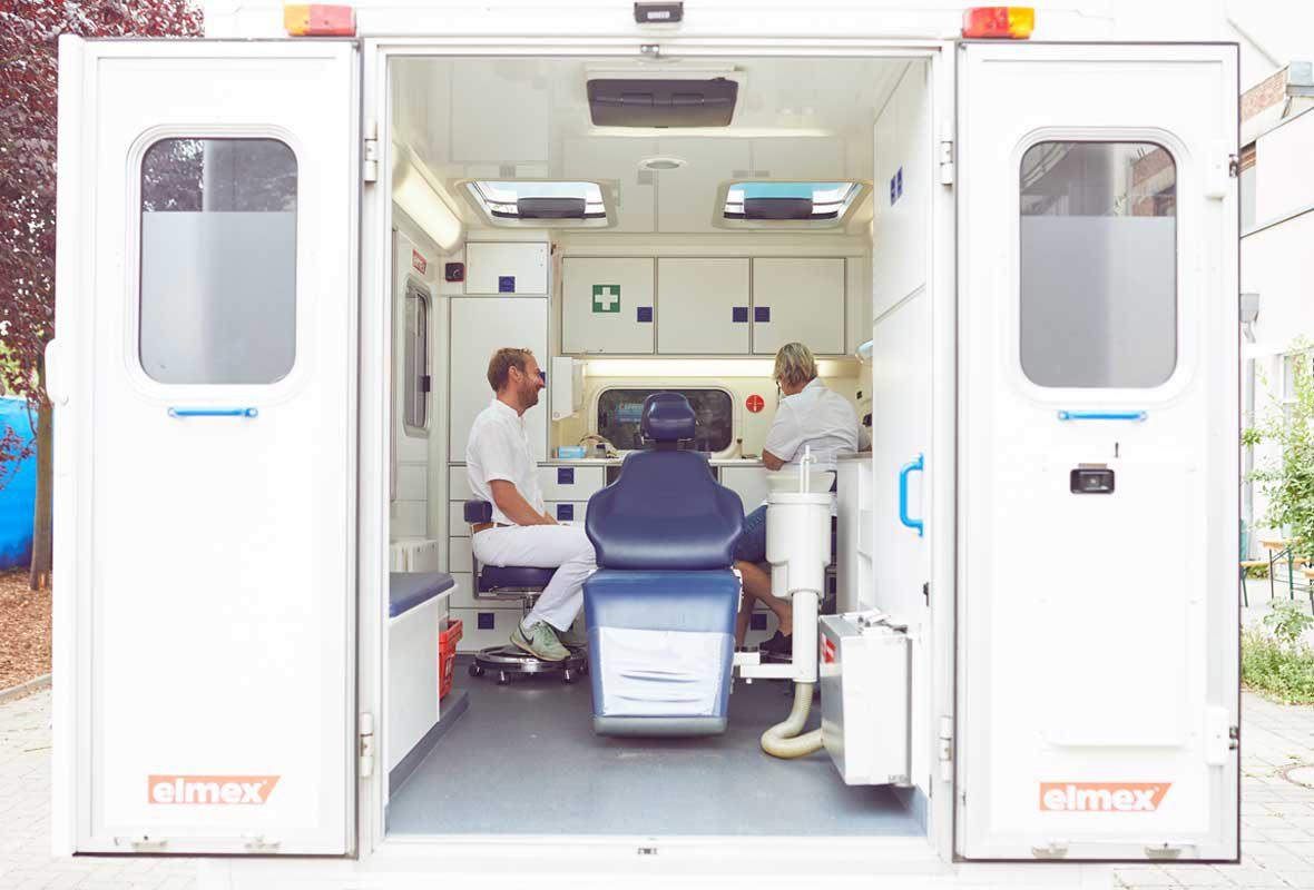 Ein Blick in das Zahnmobil der Caritas Hamburg: In der Mitte des umgebauten Krankenwagens steht ein blauer Behandlungsstuhl