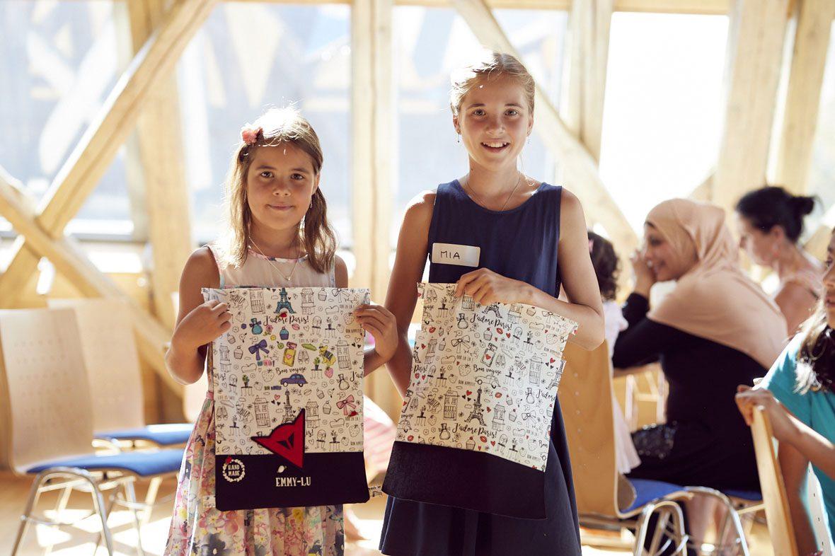 Zwei Mädchen zeigen ihre fertigen Turnbeutel.