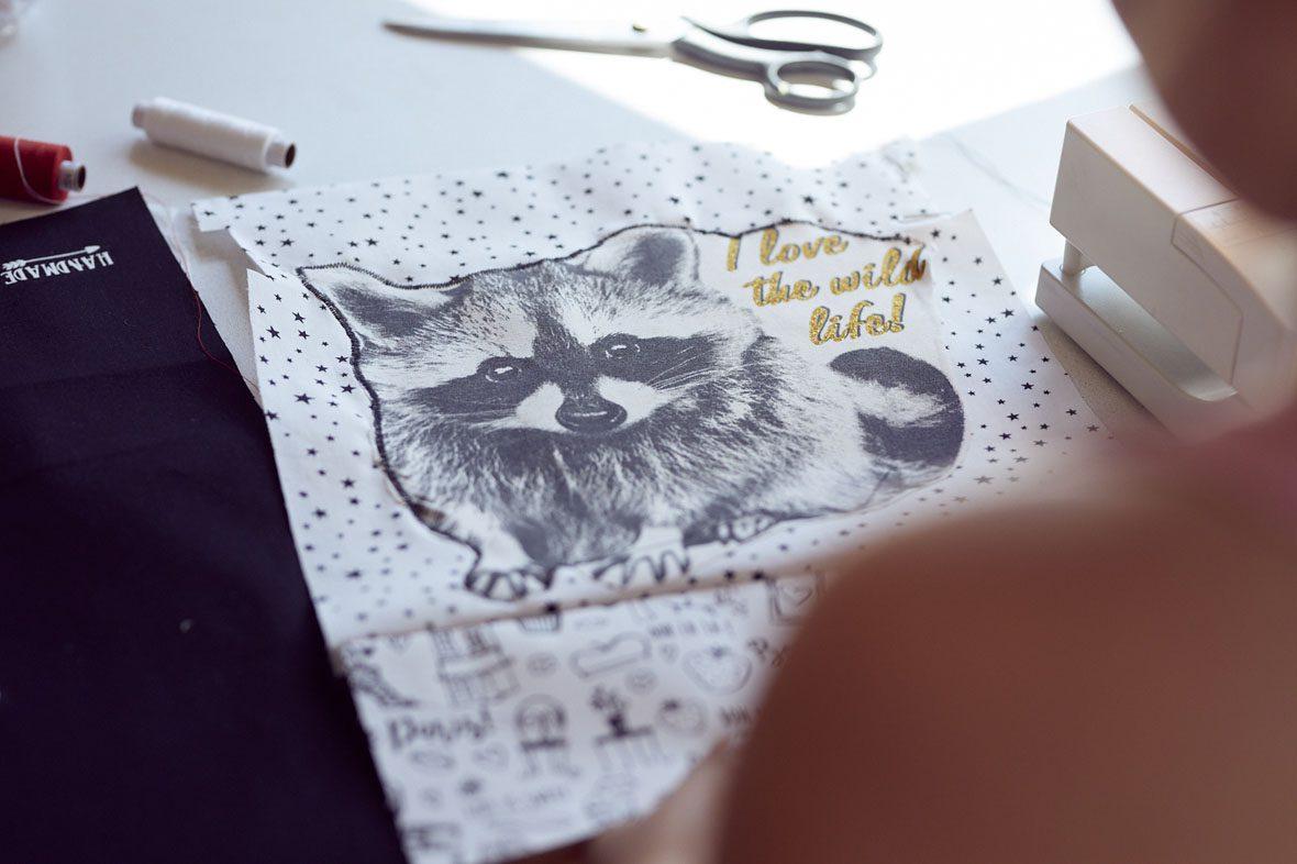 Ein Schnittmuster für den Turnbeutel liegt auf dem Tisch, darauf ein Bild von einem Waschbären und daneben der Spruch: I love the wild life!