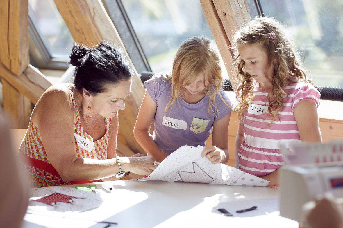 Eine ehrenamtliche Helferin unterstützt zwei Mädchen dabei, wie sie ihre Stoffe richtig aufeinanderstecken.