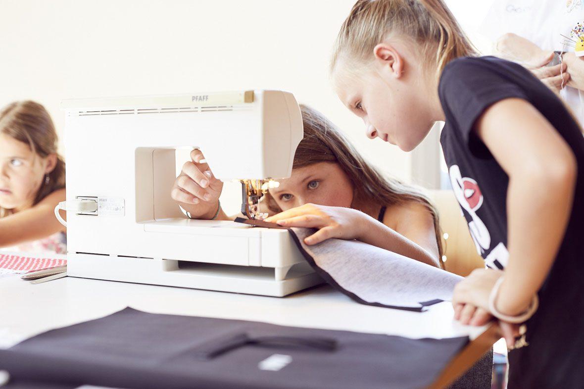 Ein Mädchen näht an der Nähmaschine, ein anderes schaut ihm dabei zu.