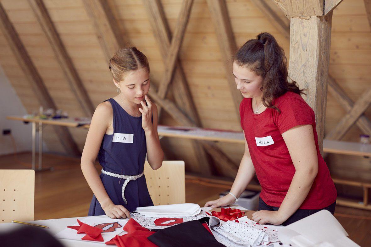 Zwei Mädchen stehen über einem Tisch mit Näh- und Bastelmaterial und wählen ihren Stoff aus.