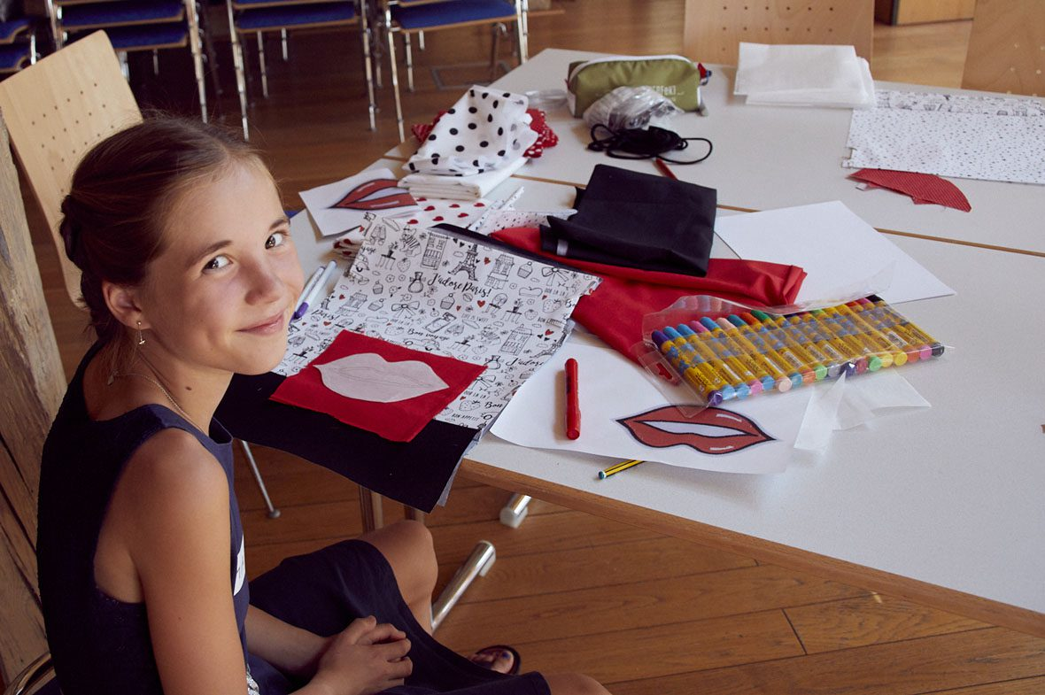 Ein Mädchen sitzt am Tisch und legt ihre Stoffreste so zusammen, dass sie ein Rechteck bilden.