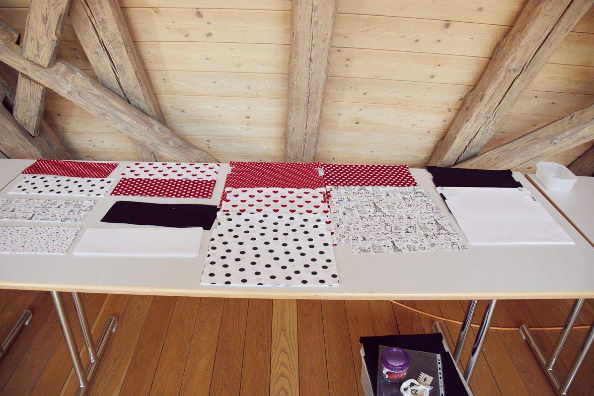 Ein Tisch voller Stoffreste: In Rot, Weiß und Schwarz.