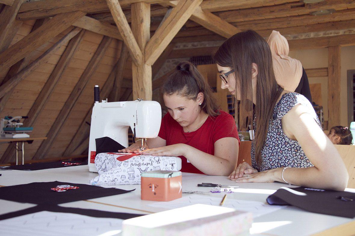 Eine Helferin unterstützt ein junges Mädchen an der Nähmaschine.