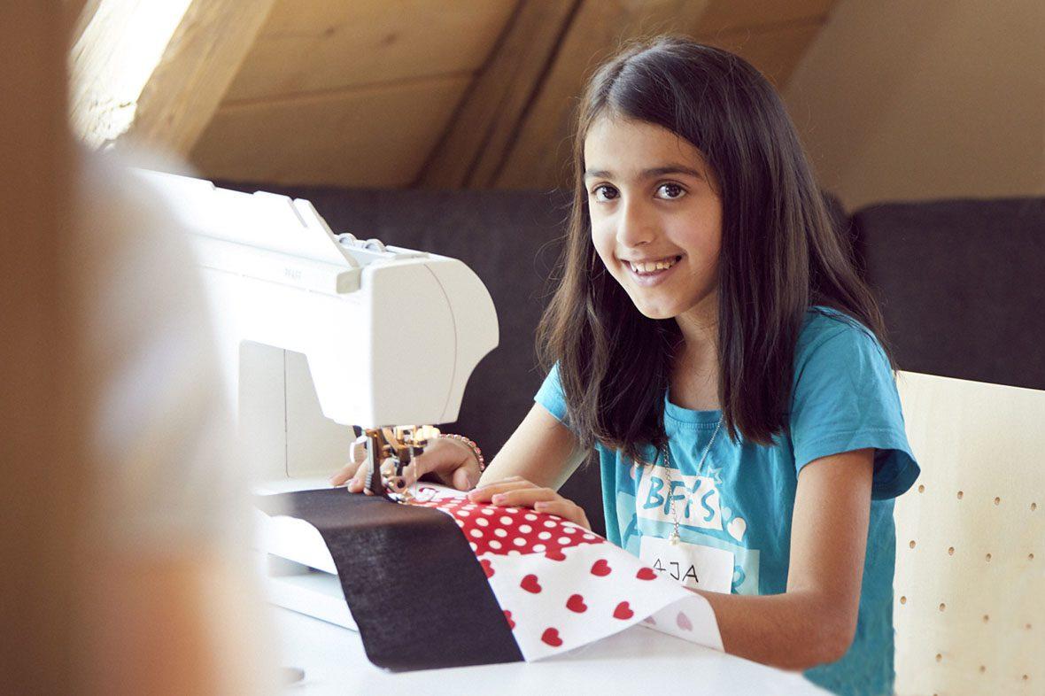 Aia sitzt an der Nähmaschine, lächelt und näht Stoffreste zu einem Turnbeutel zusammen.