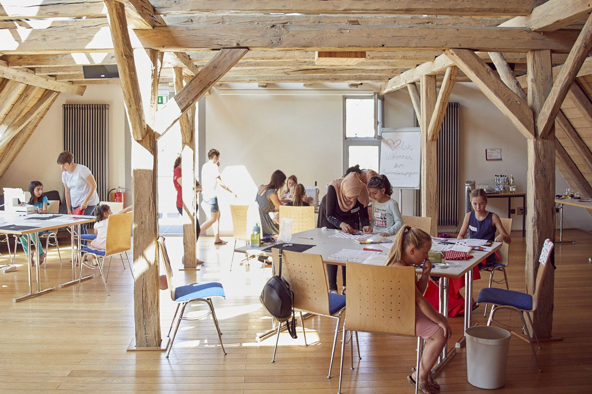 Ein Raum im Mehrgenerationenhaus Haiterbach: Er ist lichtdurchflutet, Säulen aus Holz halten die Decke. Die Kinder sitzten an Tischen vor Stoffresten.