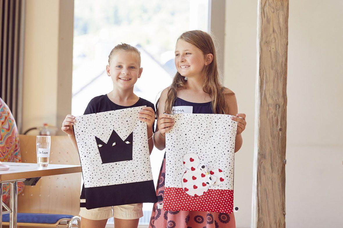 Zwei andere Mädchen zeigen ihren Turnbeutel.