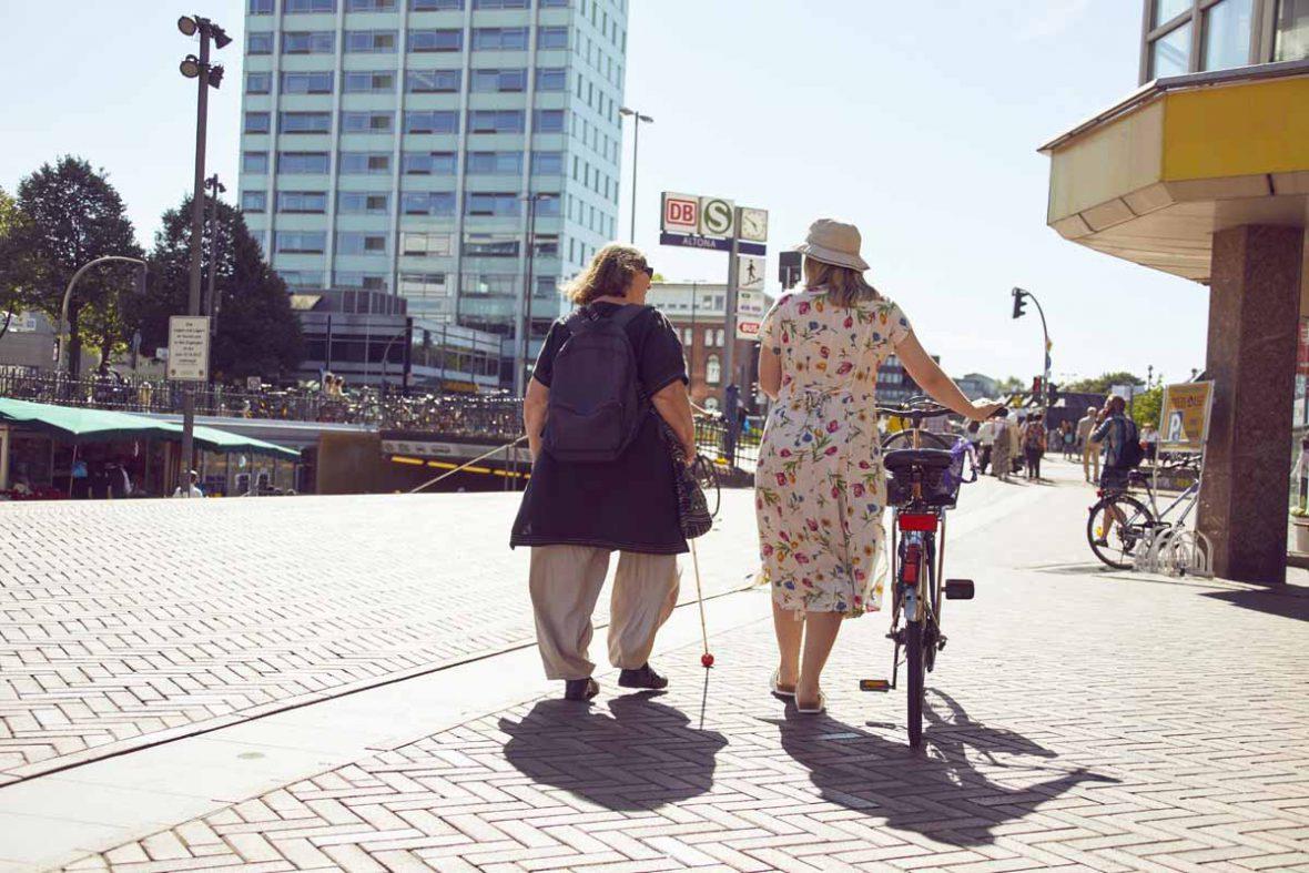 Vakil-Mai und Anna sind von hinten zu sehen. Anna schiebt ihr Fahrrad, links neben ihr läuft Vakil-Mai. Die beiden unterhalten sich.