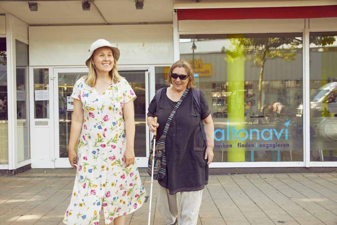 Anna und Vakil-Mai laufen mit fröhlichen Gesichtern vor der Freiwilligenagentur altonavi vorbei.