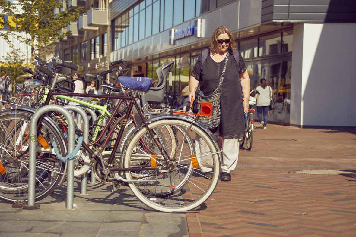 Vakil-Mai läuft an Fahrrädern vorbei, die auf den Fußweg ragen.
