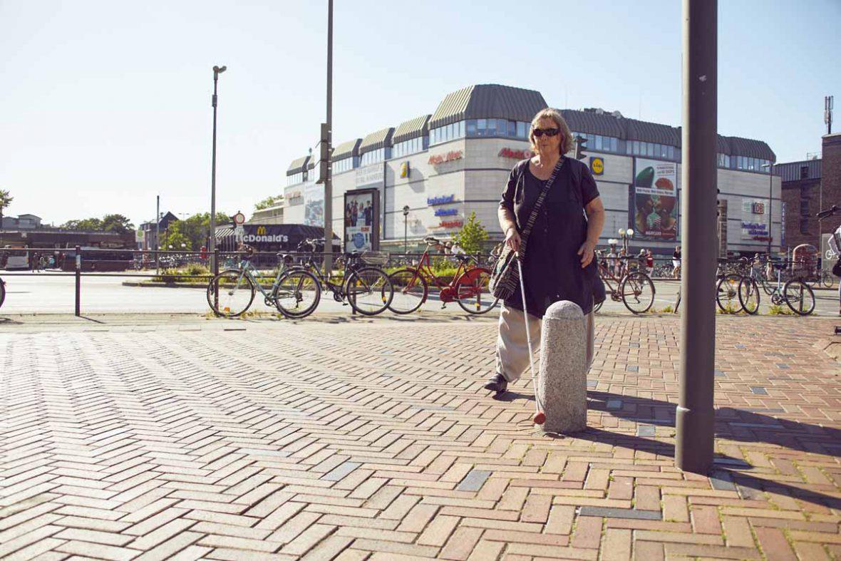 Vakil-Mai auf dem Weg durch die Fußgängerzone, ein Poller aus Stein ist in ihrem Weg.