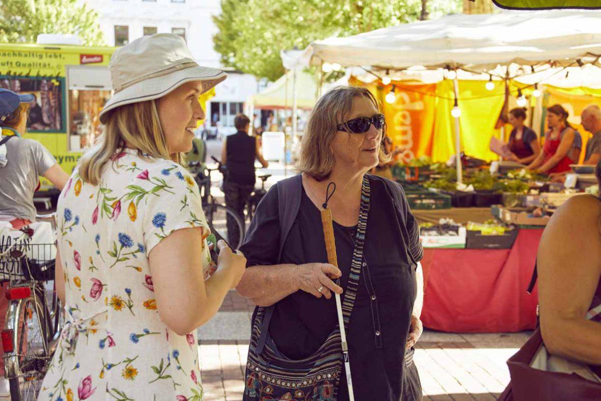 Anna und Vakil-Mai sind auf dem Markt und schauen sich die Stände an.