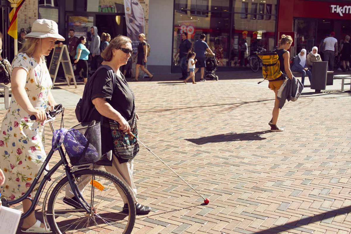 Anna schiebt ihr Fahrrad, Vakil-Mai läuft mit ihrem Blindenstock neben ihr.
