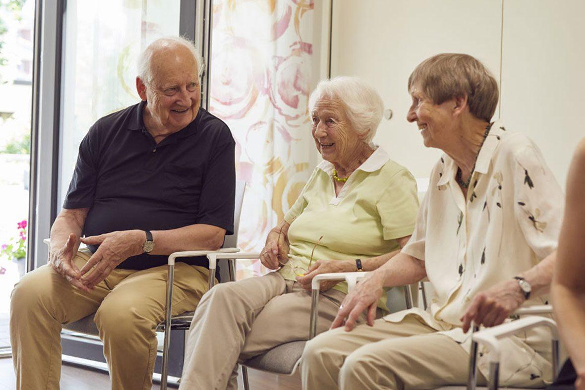 Ein Senior und zwei Seniorinnen unterhalten sich und lachen gemeinsam.