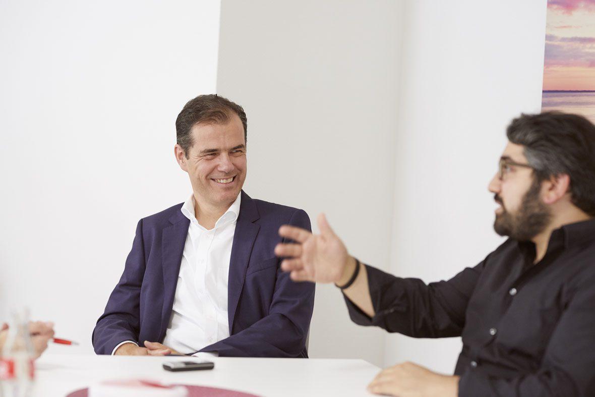 Dr. Hartmut Clausen und Manouchehr Shamsrizi unterhalten sich am Tisch.